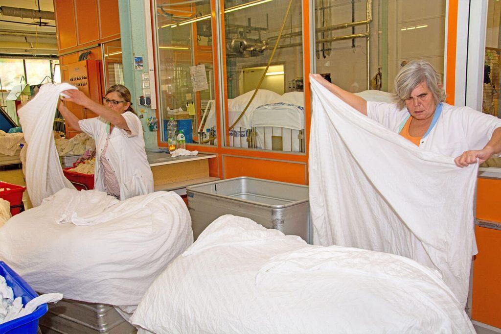 Zwei Damen die Wäsche zusammen legen